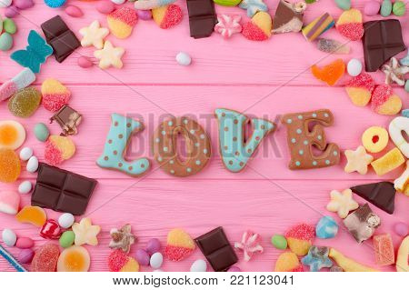 Word love from baked cookie. Colorful candies, jelly, chocolate and marmalade frame on pink background. Happy Valentines Day. Love and romance concept.