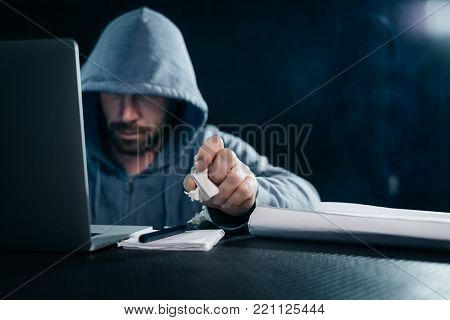 mysterious bearded male hacker doing something illegal on a laptop in the dark