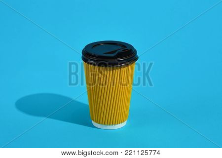 Hot coffee in yellow paper cup with black lid on blue background with shadow, blurred and soft focus image. Still life. Copy space