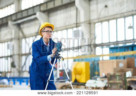 Portrait of modern young woman wearing hardhat setting up optical level mounted on tripod at construction site, copy space