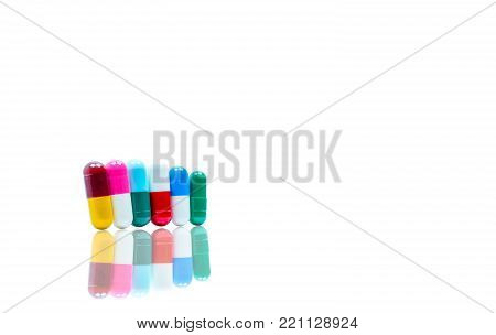Antibiotic capsules pills in a row on white background with shadows and copy space. Drug resistance concept. Antibiotics drug use with reasonable and global healthcare concept.