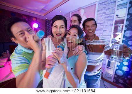Group of cheerful friends spending evening in karaoke