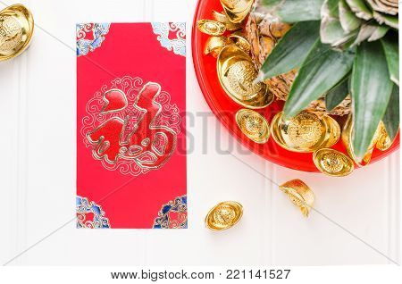 Chinese New year red envelope packet and pineapple with group of gold ingots in red tray on white wood table.on ingots mean wealthy and on envelop mean happiness