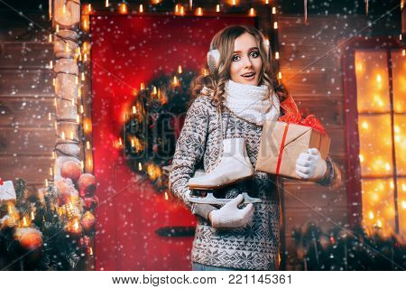Pretty girl in winter clothes is standing on the porch of a house decorated for Christmas and holding a gift box. Time for miracles.