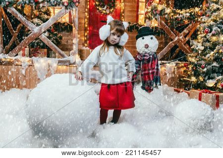 Cute child girl sculpts a snowman near her house decorated for Christmas. Merry Christmas and Happy New Year.
