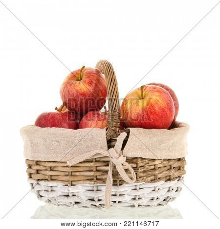 Basket full of red apples isolated over white background