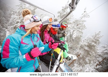 Friends in ski lift on mountain lifting on ski terrain