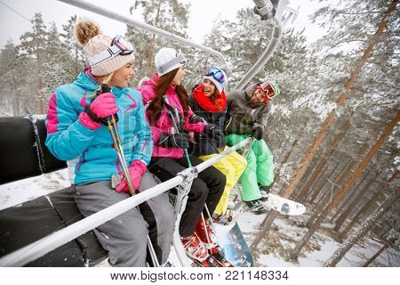 Cheerful young people lifting to ski terrain with ski lift