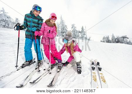 Mother with children on ski terrain preparing daughters ski shoes for skiing
