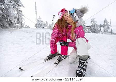 Girl kissing her mother before descend with skis