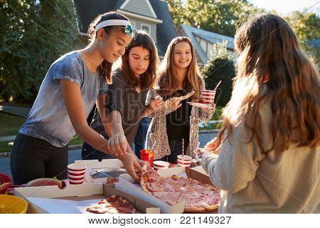 Teen girls sharing a pizza at a neighbourhood block party