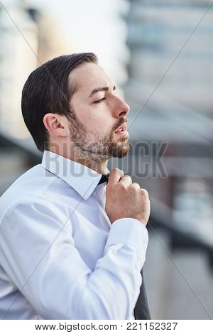 Young businessman with labored breathing from stress looses his tie knot