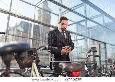 Business man with smartphone app unlocks smart lock on bicycle