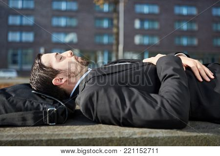 Business man is tired and takes a nap outdoors