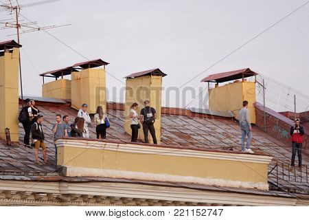 ST. PETERSBURG, RUSSIA - MAY 19, 2017: People make photo during the tour by roofs. Such tours is popular among young tourists