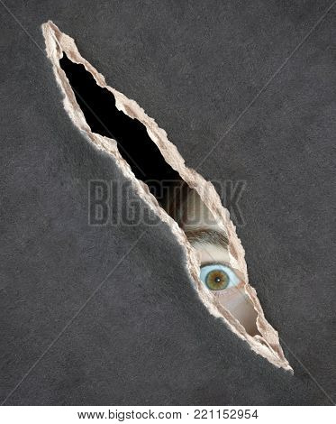 Dark series - a look from darkness. Eyes of young man looking into a hole in a paper