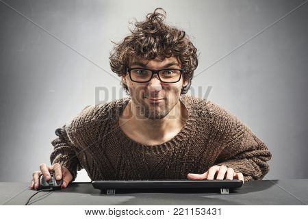 Young concentrated man playing video game on a computer. Nerd concept.