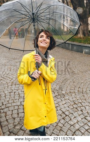 Good-looking pleased adult girl in yellow raincoat standing under big transparent umbrella, with broad sincere smile in city garden