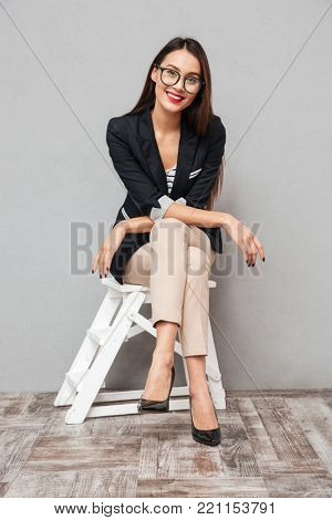 Vertical image of Pleased asian business woman in eyeglasses sitting on chair and looking at the camera over gray background