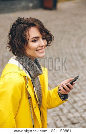 Portrait of beautiful brunette female walking on paving stones holding smartphone in hand, scrolling feed in social network