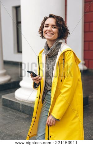 Portrait of happy joyful woman walking through street talking on her cell phone, being satisfied with good news