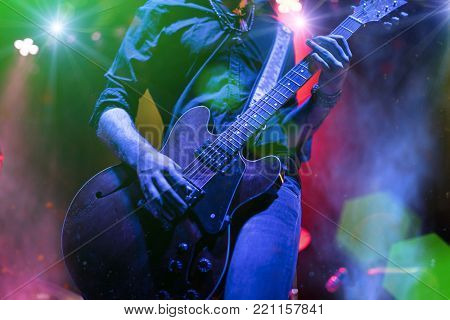 Guitarist playing on electric guitar. Rock concert stage.