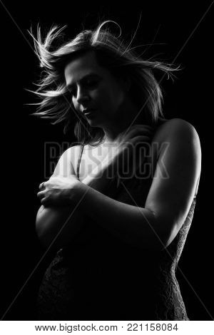 Mature woman with blowing hair in black and white with creative lighting