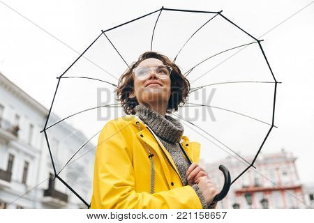 View from beneath of positive woman in yellow raincoat and glasses standing in street under big transparent umbrella, during grey rainy day