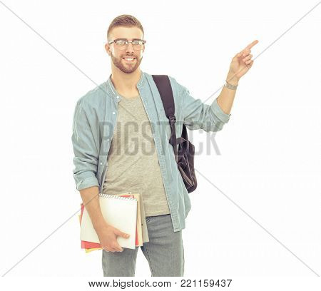 A male student with a school bag holding books and pointing isolated on white background