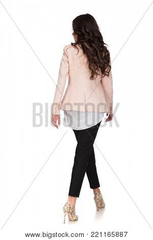 back view of a young business woman walking and looking to side on white background