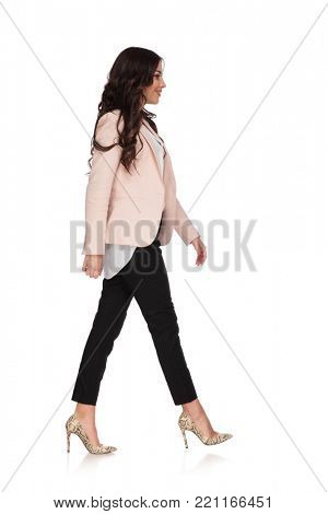 young woman in business clothes is walking and smiles on white background, side view