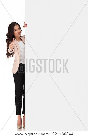 full body picture of a young business woman presenting big blank billboard and makes the ok sign on white background