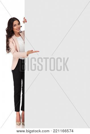 confident young business woman presenting blank board on white background, full body picture