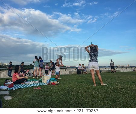 Singapore - Mar 12, 2016. People enjoying at city park in Singapore. Singapore is a global financial center with a tropical climate and multicultural population.