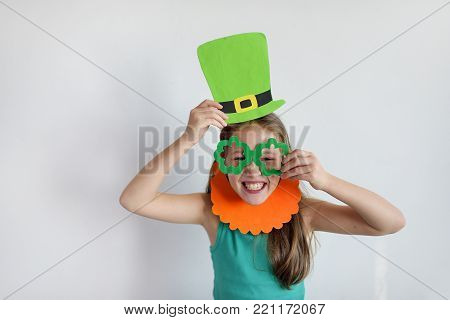 The cute girl in a mask of a leprechaun for a St. Patrick's Day