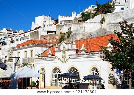 ALBUFEIRA, PORTUGAL - JUNE 6, 2017 - Market stalls with the central electric building and town building to the rear in the old town, Albufeira, Algarve, Portugal, Europe, June 6, 2017.