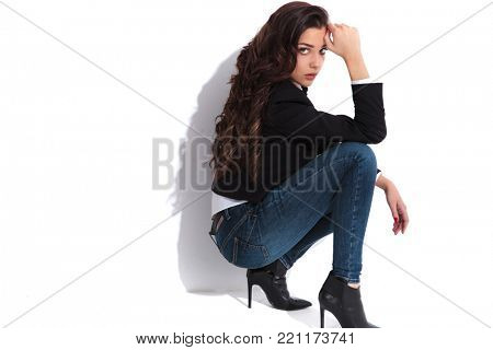 beautiful woman standing down with hand on forehead , studio picture