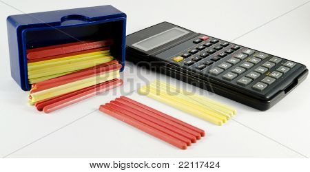 Box of counting sticks and a calculator on white background.