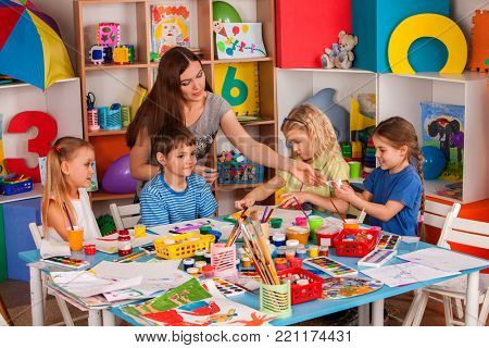 Kids playroom organization of children painting and drawing in kid's club. Craft lesson in primary school. Teaching children to do common project.