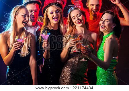 Dance party with group people dancing. Drinking game how to be an alpha male at a club. Women and confident casual smiling man have fun in night club. Seduce boozy woman cuddles up guy .