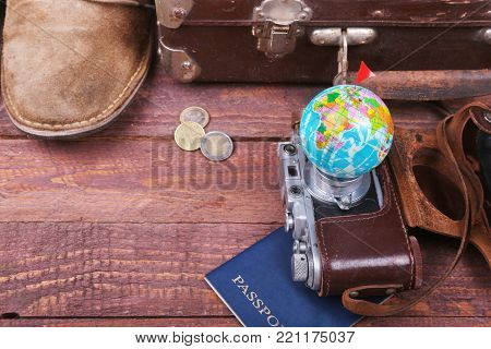 Travel concept with Vintage suitcase, sunglasses, old camera, suede boots, case for money and passport on wooden floor