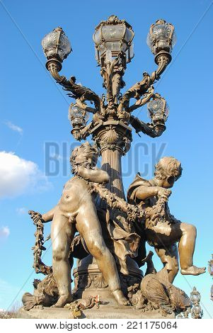 Boys nymph staue decorated under lamp or light on bridge in action standing and holds things in hand ,some fishes statue near feet with blackground blue sky and clouds.