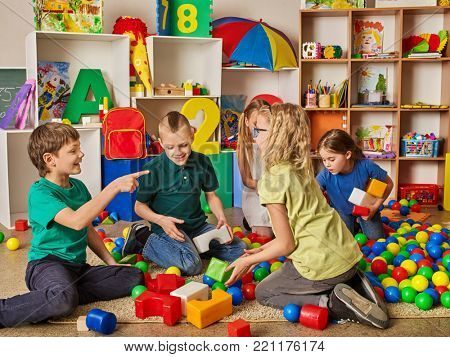 Children building blocks in kindergarten. Group kids playing toy on floor. Top view of interior preschool. Building a tower of cubes. Newcomer is getting used to new collective.