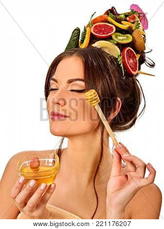 Honey facial mask with fresh fruits for hair and skin on woman head. Face of girl with beautiful face hold honeycombs for homemade organic skin and hair therapy. Treating baldness with lemon juice.