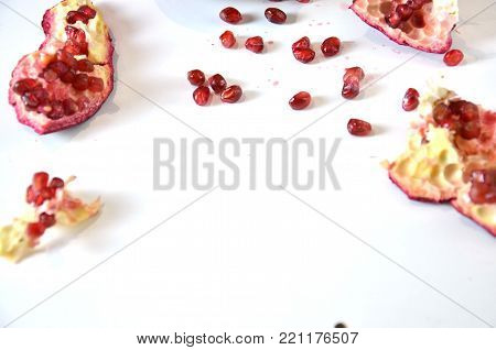 Big Ripe Red Granets or Garnets. Cut pomegranate and seeds. Fruits of Red Ripe Pomegranate on the White Background. Vegetarian Concept, Organic Vitamins, Detox. Organic and Benefit Garnet Fruit. Grains of Ripe Pomegranate.