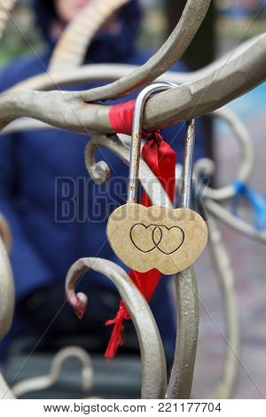 Padlock with engraving of two hearts on metal tree. Selective focus on padlock