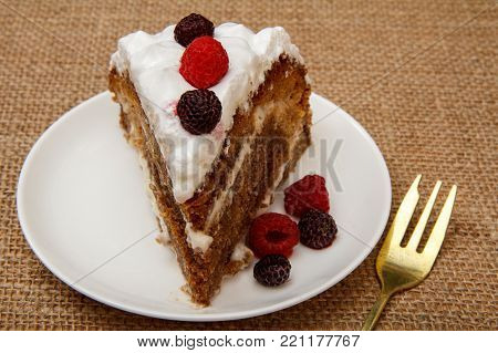 Slice of homemade biscuit cake decorated with whipped cream and raspberries on table with sackcloth