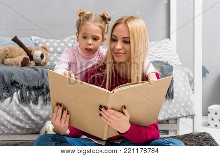 happy young mother and daughter reading book together