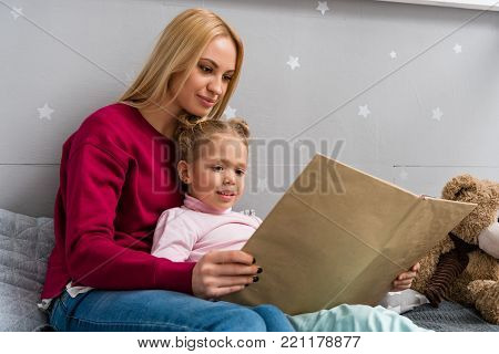 young mother and daughter sitting on bed and reading book together