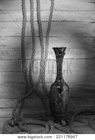 metal vase with chased pattern on the background of a wooden board with a twisted rope